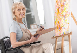 Woman in a wheelchair painting